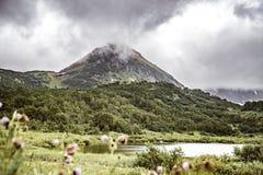 与绿色平原和湖的火山的风景堪察加半岛的,俄罗斯 免版税库存照片