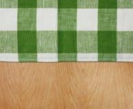 与绿色方格花布桌布的木表 免版税库存照片