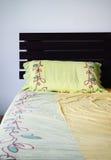 与绿色枕头的空和杂乱河床, 免版税图库摄影