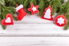 与绿色树、锥体、手工制造毛毡装饰、桔子和桂香的圣诞节横幅在白色木背景 空的空间fo 库存图片