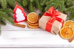 与绿色树、锥体、手工制造毛毡装饰、桔子和桂香的圣诞节横幅在白色木背景 空的空间fo 图库摄影