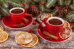 与绿色树、锥体、红色杯子用热巧克力,桔子和桂香的圣诞节横幅在白色木背景 空的空间 免版税库存照片