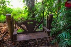 与绿色树的一把木椅子对后面 免版税库存照片