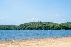 与绿色树的湖旁边大海 免版税库存图片