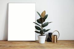 与绿色植物的绝尘室内部在土气木桌,现代个人膝上型计算机,在框架的海报上与布局的空间 库存照片
