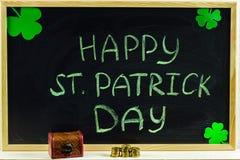 与绿色白垩的题字在黑板:愉快的圣帕特里克的天 三叶草叶子 与硬币的胸口 免版税库存图片