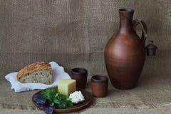 与绿色的干和软干酪在圆的黏土板材、水罐酒的,杯子和面包在白色布料在手织的概略的背景 免版税库存照片