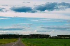与绿色的风景调遣空的高速公路 免版税图库摄影