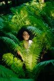 与绿色眼影膏和唇膏的引诱的年轻非洲模型在蕨中 肉欲的纵向 图库摄影