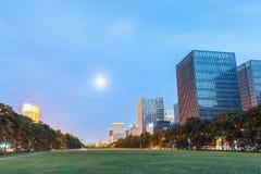 与绿色空间的现代大厦在黄昏 图库摄影