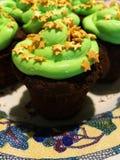 与绿色结霜和金黄星的巧克力杯形蛋糕在一块白色马赛克被仿造的板材洒 库存照片