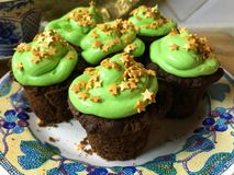 与绿色结霜和金黄星的杯形蛋糕在一块白色板材洒 免版税库存图片