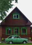 与绿色老汽车的五颜六色的老木村庄 免版税库存图片