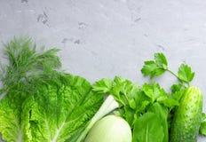 与绿色菜、沙拉、黄瓜、大葱和夏南瓜的背景在灰色石桌上 免版税库存照片