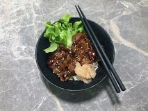与绿色菜和烂醉如泥的姜的烤猪肉米在黑碗 免版税图库摄影