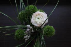 与绿色蓬松康乃馨、一柔和的大毛茛属和草的美丽的黑暗的花束在黑木背景 免版税库存照片