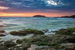 与绿色青苔的自然海景包括岩石、被弄脏的波浪、海岛和五颜六色的云彩在日出 免版税图库摄影
