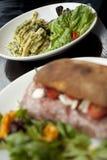 与绿色Pesto和沙拉的面团盘在一块白色板材 免版税库存照片