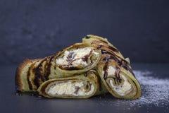 与绿色spirulina的自创薄煎饼和巧克力被充塞的白色酸奶干酪用在黑板岩背景的葡萄干,关闭 库存图片