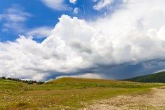 与绿草和剧烈的顶上的暴风云的小山 免版税库存图片