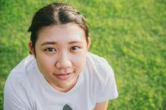 与绿草的逗人喜爱的年轻无辜的亚洲青少年的微笑 免版税库存照片