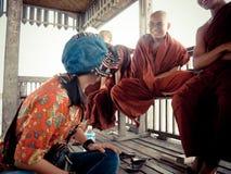 与缅甸修士的泰国妇女坐和谈话U Bein桥梁的 免版税库存图片