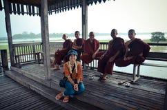 与缅甸修士的泰国妇女坐和谈话U Bein桥梁的 免版税库存照片