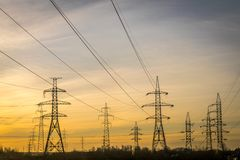 与缆绳和导线的电定向塔在黎明或黄昏 免版税库存照片