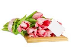 与缎丝带的桃红色郁金香在与明信片的木制框架 库存图片