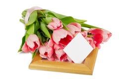 与缎丝带的桃红色郁金香在与明信片的木制框架 免版税库存图片