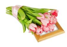 与缎丝带的桃红色郁金香在木制框架 图库摄影