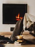 与编织地毯、书和茶的摇椅或咖啡在壁炉前 库存图片