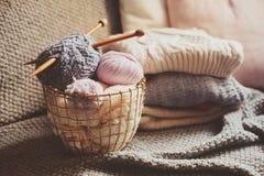 与编织针的灰色和桃红色毛线球在与被编织的毛线衣的金属篮子在背景 免版税图库摄影