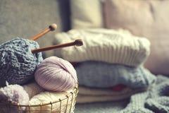 与编织针的灰色和桃红色毛线球在与被编织的毛线衣的金属篮子在背景 免版税库存照片