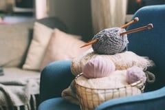 与编织针的灰色和桃红色毛线球在与被编织的毛线衣的金属篮子在背景 免版税库存图片