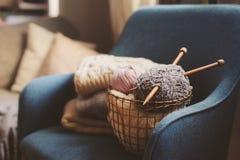 与编织针的灰色和桃红色毛线球在与被编织的毛线衣的金属篮子在背景 库存照片