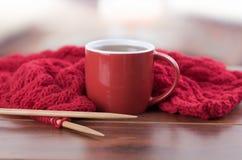 与编织针的特写镜头红色毛线球和围巾过程中说谎在书桌,坐在它旁边的咖啡杯上,模糊 免版税库存照片