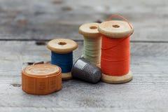 与缝合的工具和色的螺纹的背景 免版税库存照片