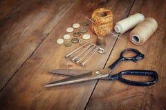 与缝合的工具的葡萄酒背景和在木织地不很细背景的针线包 图库摄影