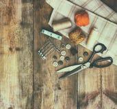 与缝合的工具的葡萄酒背景和在木织地不很细背景的针线包 免版税库存照片