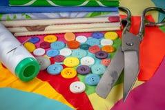 与缝合的辅助部件的背景,有色的彩色印花布的,按钮,剪,针线的集合 免版税库存图片