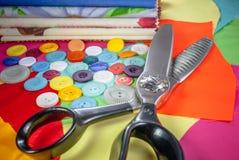 与缝合的辅助部件的背景,有色的彩色印花布的,按钮,被加锯齿的剪,为针线设置了 库存照片