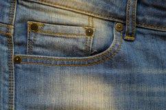 与缝的蓝色牛仔布,螺柱和牛仔裤为背景装在口袋里 免版税库存图片