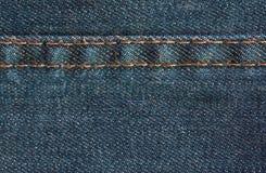 与缝,背景的蓝色牛仔布牛仔裤纹理 库存图片