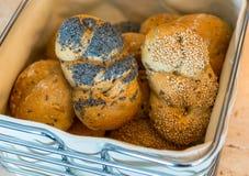 与罂粟种子和芝麻的手工制造辫子与在篮子的其他小圆面包 免版税库存图片
