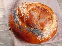 与罂粟种子和芝麻的麦子大面包在木桌上 库存照片