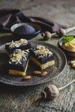 与罂粟种子层数的松糕,装饰用白色巧克力卷毛和切的杏仁 库存照片