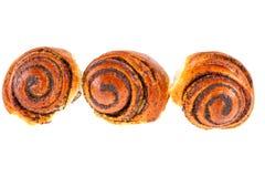 与罂粟种子的三个鲜美卷小圆面包在白色背景 库存图片