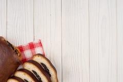 与罂粟种子的小圆面包在厨房餐巾和一张老木桌 图库摄影