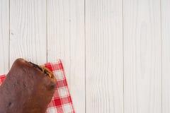 与罂粟种子的小圆面包在厨房餐巾和一张老木桌 免版税库存图片